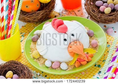 Easter chicken fondant cake on festive decorated table Easter food idea for kids Easter colorful food composition