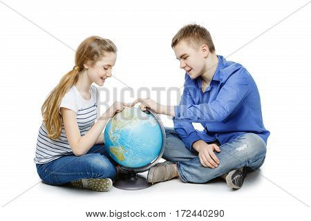 Beautiful teen boy and girl in casual clothes sitting on floor looking for something on the Earth globe. Isolated on white background. Copy space.