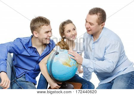 Beautiful teen boy and girl in casual clothes sitting on floor with father looking for something on the Earth globe. Isolated on white background. Copy space.