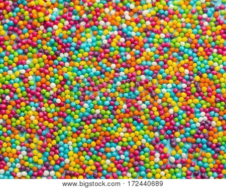 Colorful sugar sprinkles dots as a background rainbow sprinkles ice cream cake dessert baking topping concept Easter background