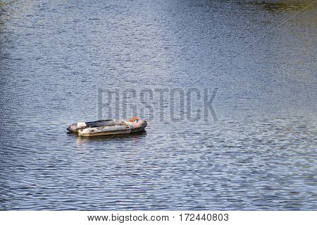 Oporto Portugal - 2016 July 21th: Empty single inflatable dinghy with outboard motor lies at anchor in a harbor of Duoro river Portugal