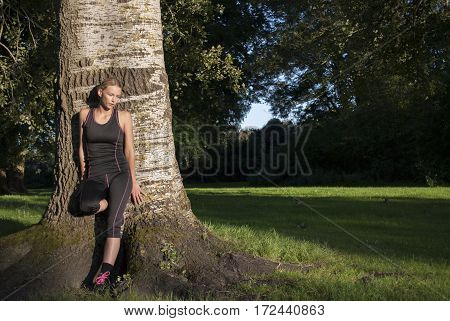 pretty young woman leaning against tree in park to cool down after running