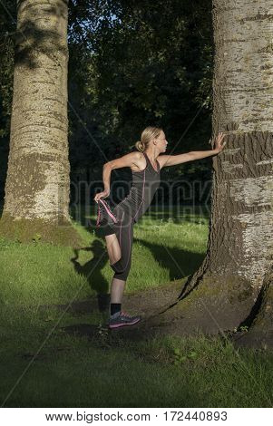 Beautiful young woman doing stretching exercises for quadriceps in park during sundown in summer