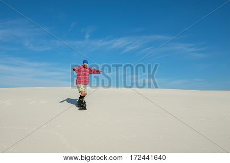 Joyful Man Slides Down On A Snowboard On The Sand Dune