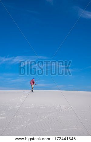 Man With Snowboard Goes Through The Desert