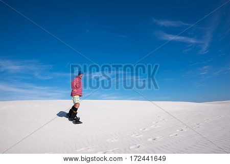 Smiling Man Slides Down On A Snowboard On The Sand Dune