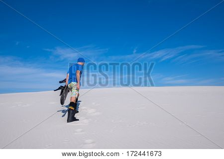 Man In Blue Cap With A Snowboard Climbs Up The Sand Dune