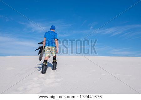 Guy In Blue Shirt With A Snowboard Climbs Up The Sand Dune