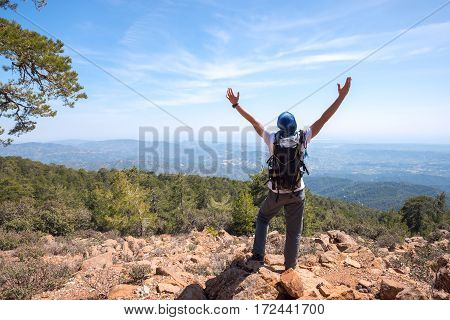 Happy Man With Backpack Stands On A Rocky Slope