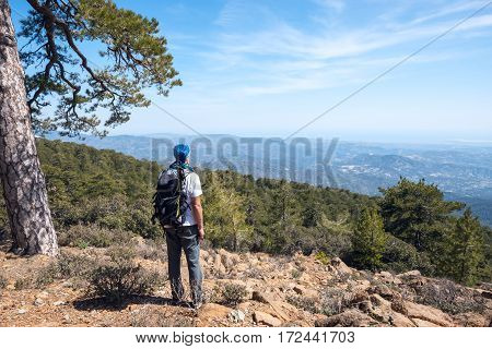 Traveler With Backpack Stands On A Rocky Slope