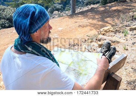 Bearded Man Exploring A Map And Considers Route