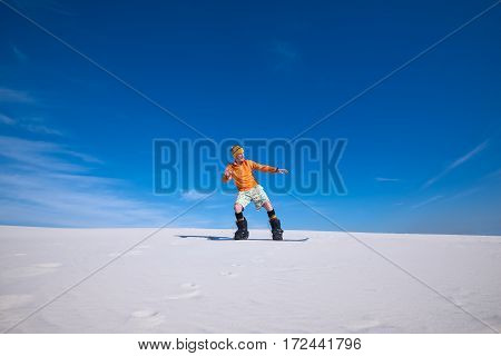 Sporty Man Rides On The Snowboard In The Sand Dunes
