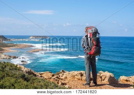 Traveler with backpack standing on the rocky sea shore and watching the surf. Sunny day on the peninsula Akamas Cyprus. Back view.