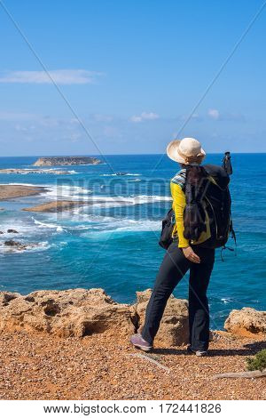 Woman traveler with backpack standing on the rocky sea shore and watching the surf. Sunny day on the peninsula Akamas Cyprus. Back view.
