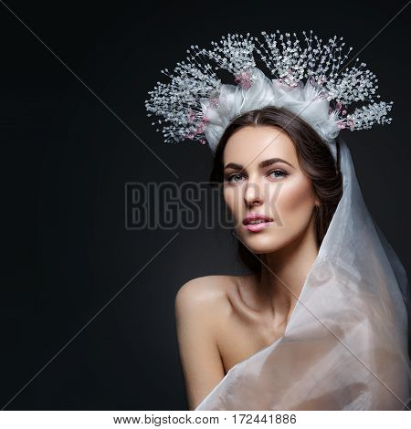 Beautiful young brunette woman in crystal crown and white veil on black background. Romantic beauty look. Copy space.