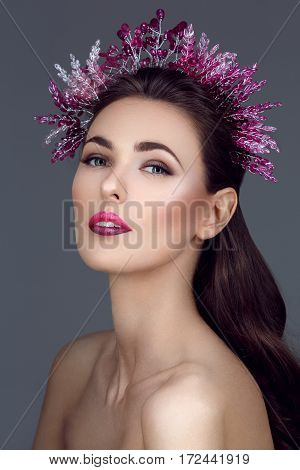 Beautiful brunette young woman with purple make-up and crystal head piece. Different colors upper and lower lip. Beauty shot.