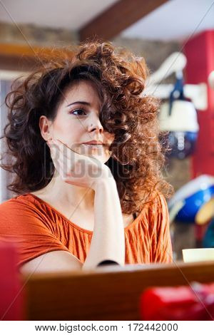 young woman with long curly hair at hair studio looking at mirror