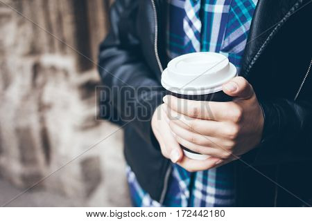 Young woman is drinking coffee on the street. Close-up of hands with white and black take away cup of hot coffee. Early morning routine. Hot cup of coffee while walking outside in the city center. Copy-space blank for your advertisement text or design con