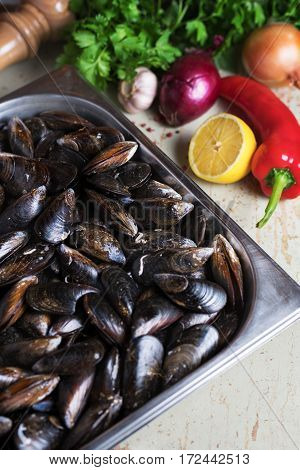 Fresh mussels with ingredients for cooking on rustic background, top view, border. Seafood concept, vertical shot.