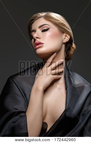 Portrait of beautiful young woman with cat eye make-up in black fabric. Studio beauty shot over black background.