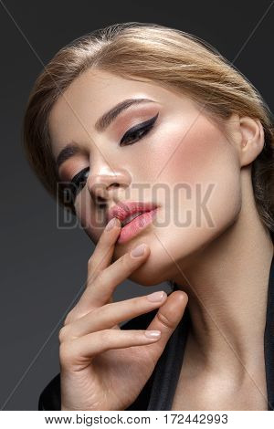 Portrait of beautiful young woman with cat eye make-up. Close-up studio beauty shot over black background.