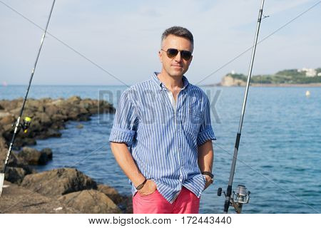 Handsome man. Outdoor male portrait. Middle-aged man resting at seafront, summer outdoor portrait, image toned. Fishing.