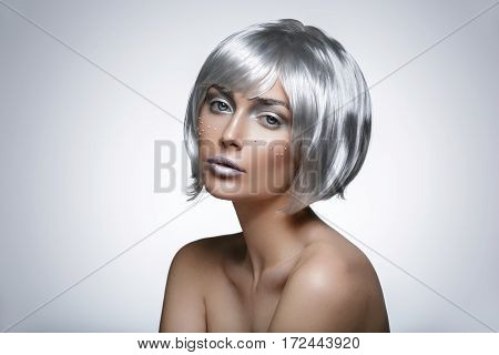 Beautiful young woman with glowing skin, fashion make-up in short silver hair wig. Beauty shot on white background. Copy space.