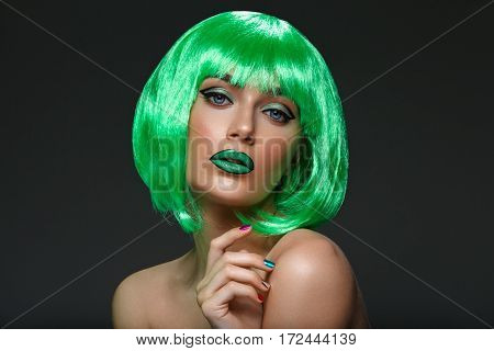 Beautiful young woman with glowing skin, fashion make-up and metallic nails in short green hair wig. Beauty shot on black background. Copy space.