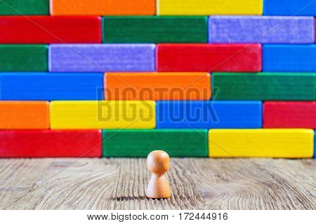 Abstract man standing in front of a wall or barrier of multicolored wooden blocks. Success concept. Business metaphor.