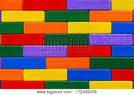 Multicolored wood background. Background with colorful shapes wooden blocks. Colorful wall toy colored wooden bricks. Multicolor wooden blocks.