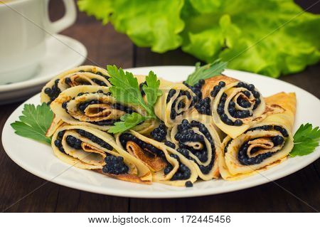 Rolls Pancakes With Black Caviar. Russian Cuisine. Flat Lay. Maslenitsa. Wooden Background. Close-up