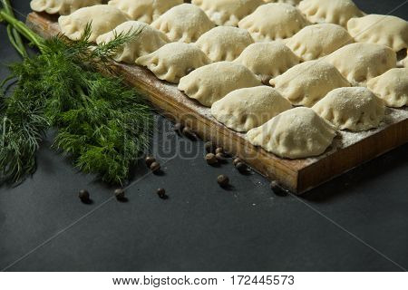 Dumplings On A Black Background With Fresh Herbs And Vegetables. Homemade Food. Traditional Russian