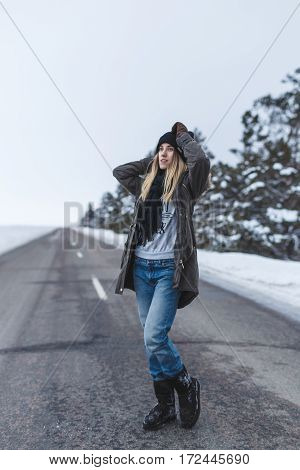 Girl is standing on the winter road Christmas trees around with the snow on the branches