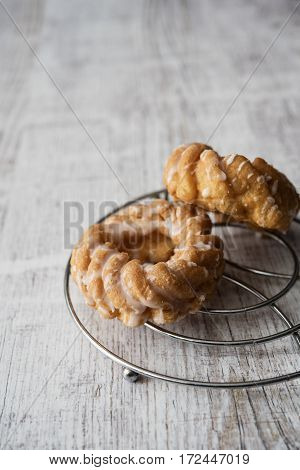 Sweet donuts with icing on wooden background