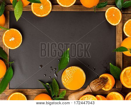Orange juice with squeezed orange fruits on a chalkboard.