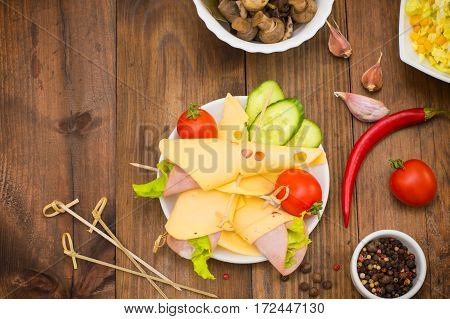 Slices Canape With Cheese, Sausage, Greens And Tomato. Wooden Background. Top View. Close-up