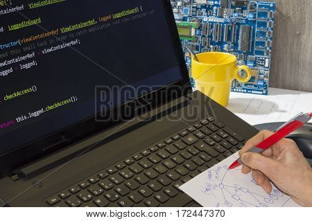 a person writing programming code on laptop computer