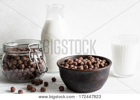 chocolate cornflakes bowl in a bowl with milk for breakfast on white wooden background