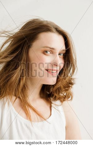 Portrait of a young woman with brown hair in a white shirt on a white background. Woman smiling. A woman without makeup. Model test. Fashion model. Type a strong face.
