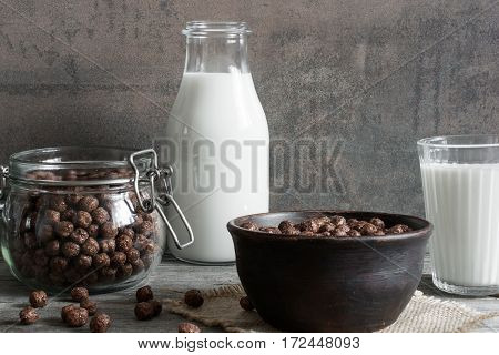 chocolate cornflakes bowl in a bowl with milk on rustic wooden background. breakfast