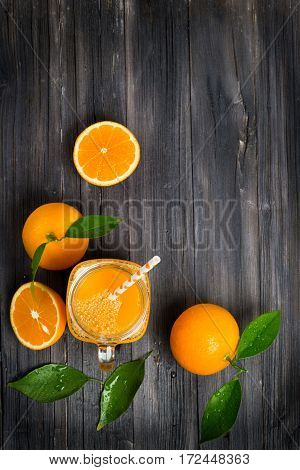Top view of freshly squeezed orange juice in a mason jar and fresh oranges fruits with green wet leaves on a wooden rustic table with copy space.