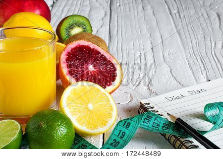 Fitness concept with fruits and fresh juice. Fitness motivation with centimeter and notebook on white wooden background. close up