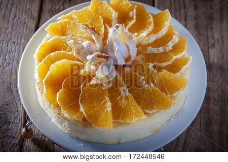 Cheesecake decorated with oranges and physalis on a table