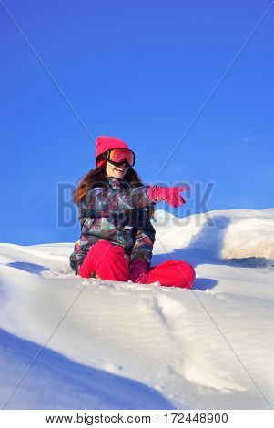 Happy girl sitting on top of a snowy mountain