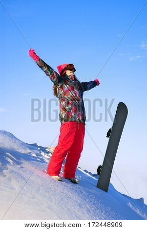 happy girl standing on a mountain top with snowboard