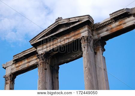 Parthenon in Athens, Greece. Photo taken in December 2016. Blue sky with stone figure in foreground.