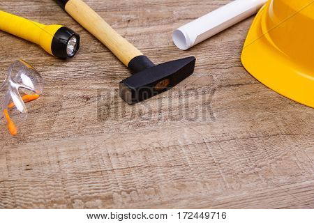 Helmet, hammer and protective glasses. Paper plan and flashlight. Wood rustic background.