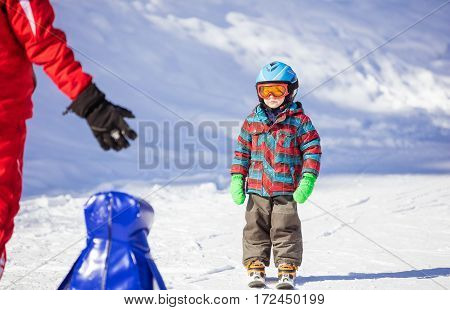 Young skier looking at ski instructor while sliding down mountain slope. Ski lesson in alpine school.