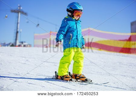 Little boy skiing downhill wearing safety helmet and goggles