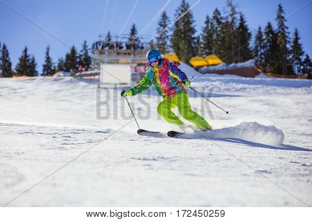 Male skier carving turn on mountain chairlift in background
